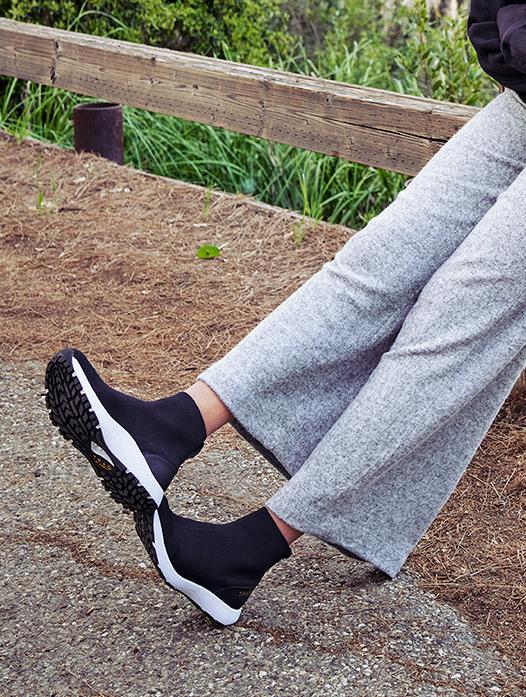 スマートウォーキングシューズを履いて脚の伸ばし休憩する女性