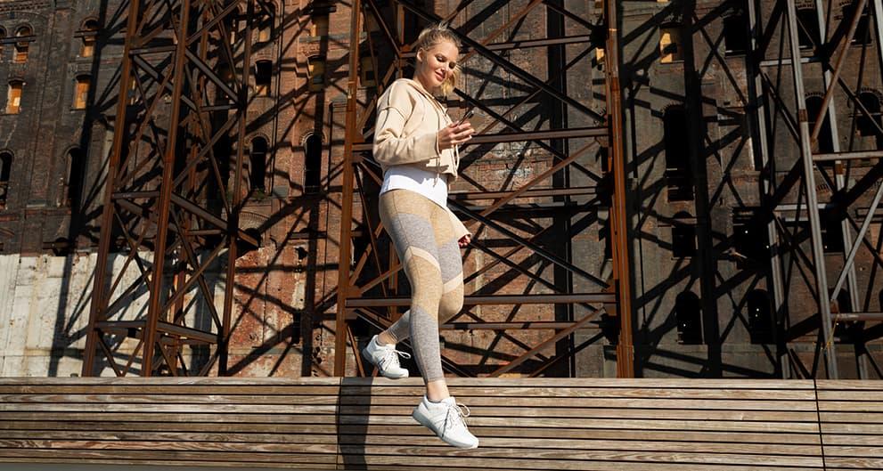 スマートウォーキングシューズを履いて階段を下りる女性