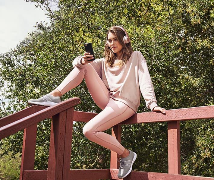 スマートウォーキングシューズを履いて座り込みスマートフォンを操作する女性