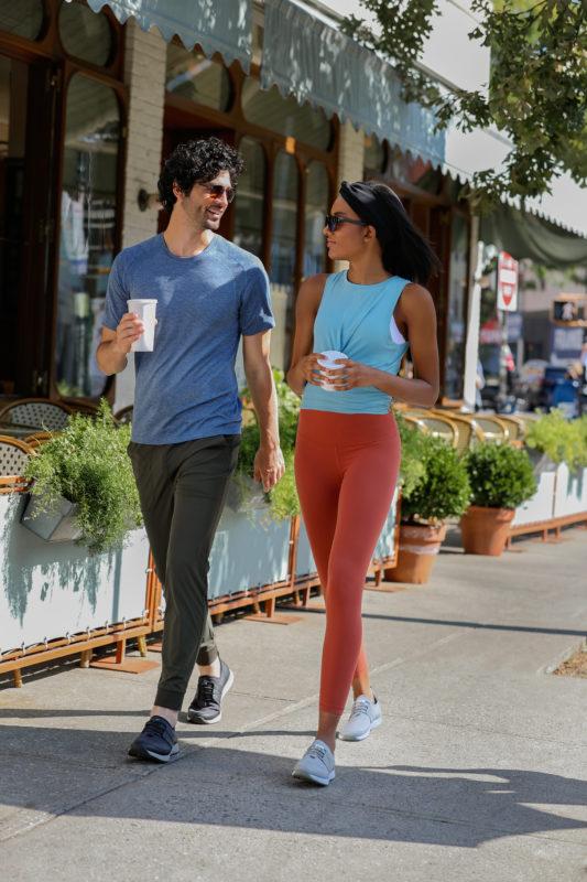 男女が夏のコーヒー飲みながら散歩している